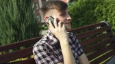 banquette : young man talking on the phone in park Stock Footage
