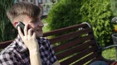 banquette : serious young man talking on the phone in park Stock Footage