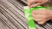 Woman hands untie green ribbon on gift box. Lockdown shot of tender female hands unpacking present on wooden table. Personal perspective of lady unpacking box. 4k UHD.