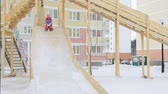 fast ice : Child is riding slides at playground Stock Footage