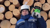 pracovníků : Worker with chain saw against pile of logs