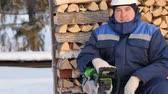 renewable : Worker with chain saw against pile of logs