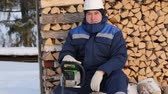 kask : Worker with chain saw against pile of logs