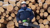 lumbering : Worker with chain saw against pile of logs