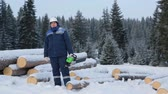 lumbering : Worker with chain saw near pile of logs in the forest