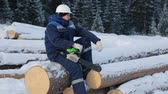 kask : Worker sitting on pile of logs in the forest Wideo