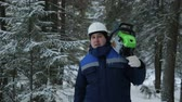 lumbering : Worker with chainsaw on shoulder looking around in winter forest Stock Footage