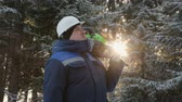lumbering : Worker with chainsaw on shoulder looking up in winter forest