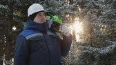 kask : Worker with chainsaw on shoulder looking around in winter forest Wideo