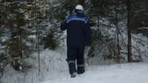 lumbering : Worker with chain saw on shoulder going through winter forest