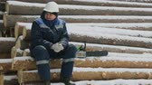lumber industry : Worker resting on big pile of logs in winter forest