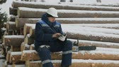 датчик : Worker with tablet computer on big pile of logs in winter forest