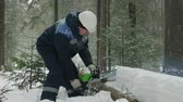 dym : Worker sawing with chainsaw in winter forest