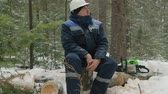 fűrész : Worker resting on log in winter forest