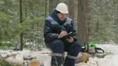 supervise : Worker with tablet working in winter forest