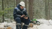 lumber industry : Worker with tablet computer working in winter forest