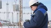 supervise : Engineer with portable computer at electric power station Stock Footage