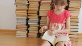 strana : Little girl reading on background of books