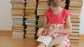 okumak : Little girl reading on background of books
