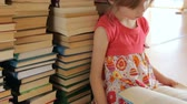 обогатительный : Little girl reading on background of books