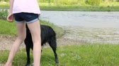 yalan : Girl with her dog by the river Stok Video