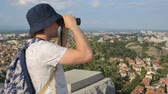 panama city : Young male tourist looking through binoculars above the city