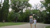 kamu : Woman with daughter walking in park Stok Video