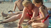 suntan : Woman with little girl playing with sand on beach