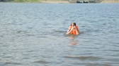 kurtka : Girl in life jacket in water