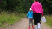 fir : Woman with little girl walking in forest
