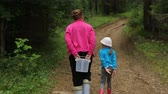 Woman with little girl walking in forest