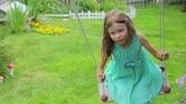 sukienki : Little girl swinging in garden Wideo