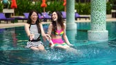 slow motion of two women friends splashing water in swimming pool