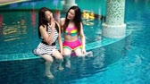 slow motion of two women friends enjoy in the swimming pool