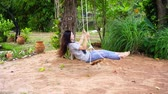 slow motion of woman playing on swing in garden