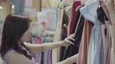 kleerhanger : young woman shopping in a clothing store Stockvideo