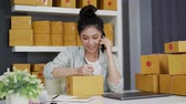 endereço : small online business owner talking with customer on a mobile phone and writing address on parcel box at home office