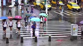 deštivý : Taipei, Taiwan- 11 June, 2019: slow-motion of people crossing street in front of Ximending Shopping District with falling rain in Taipei, Taiwan. Ximending is the famous fashion, night Market and street food in Taipei.
