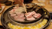 pauzinho : slow-motion of hands are using chopsticks to grilled pork barbecue