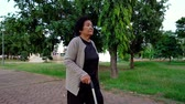 canne : slow-motion of senior woman walking with walking stick in the park