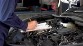 mechanic hand checking and repair service a car with clipboard