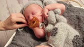 Cute baby sucking a soother, mother fixing and comforting him in his sleep, with toy Стоковые видеозаписи