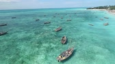 Rustic wooden boats for fishing sitting in calm waters of Zanzibar, Tanzania, aerial