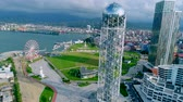 Batumi, Georgia - 27 August 2017: Aerial video from a flying drone of the Alphabet tower and seaside promenade in Batumi, Georgia Стоковые видеозаписи