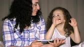 sólido : Mom, along with her little beautiful daughter, reads with grace the tales of the night, plunged into the history, her mother explains interestingly, and already the daughter tells and composes actress. 4K. Stock Footage