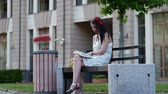 sólido : A pretty girl with a red rim on her head sits on a park bench and reads a book, and in the background.