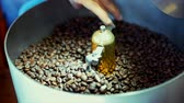 desenvolver : Mixing of roasted coffee. Partial removal of bad grains. The roasted coffee beans got on the mixer sorting by a professional machine. Slow motion.