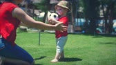 helpful : Cute little boy playing with a soccer ball running to his mother in a hug. Stock footage.