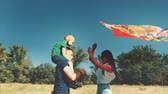 piggyback : Happy family, mom, dad and son are walking in nature, launching an air snake. Stock footage.