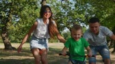 piggyback : Happy family, mother, father and son are walking by nature, the child is riding a bicycle, his parents help him to accelerate. Happy parents and the baby are smiling. The video. Stock Footage